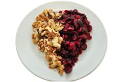 Heart Healthy Snack. Dried Cranberries with walnuts on a white plate in a heart shape present themselves as a healthy snack royalty free stock image