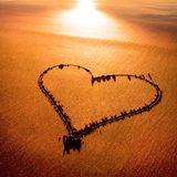 Heart. Heard drawn in the sand on the shinning gold sandy atlantic coast before the sunset Stock Photo