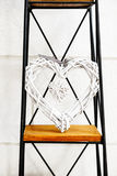 Heart within a heart decorative prop standing on metal and wooden stand against the white wall Stock Photo