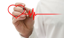 Heart and heartbeat symbol. Male hand drawing heart and heartbeat symbol with red pen royalty free stock image