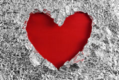 Heart hole in aluminum foil Royalty Free Stock Photography