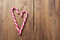 Heart in honor of Valentine`s day made from candy cane on a background of old wooden planks Royalty Free Stock Images