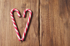 Heart in honor of Valentine`s day made from candy cane on a background of old wooden planks Royalty Free Stock Photos