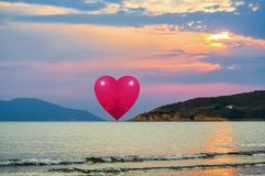 Heart on the horizon. Floating heart on the horizon during the gloomy sunset over the sea royalty free stock photos