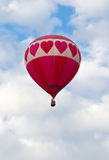 Heart Hot Air Ballon flying in the Clouds. A heart hot air balloon fling in the clouds with a touch of blue sky royalty free stock photography