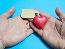 Heart in human hands with empty label. Donor organ donation list royalty free stock photo