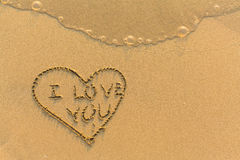 Heart and I Love You - hand-drawn in gentle sea beach sand. Abstract. Stock Image