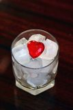 Heart in ice. Red heart in glass with the cubes of ice royalty free stock photography