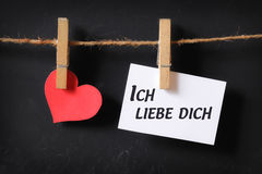 Heart with ich liebe dich poster hanging. With blackboard background Royalty Free Stock Image