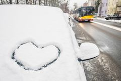 Heart icon drawing in snow on car front window, bus in the background. Love winter symbol stock photos