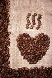 Heart illustration made of fresh, aromatic coffee beans. On cloth vintage background with coffee beans frame Royalty Free Stock Photos