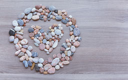 Heart inside a circle of colorful pebbles on wooden surface. Bac Royalty Free Stock Photography