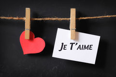 Heart with je t'aime poster hanging. With blackboard background Royalty Free Stock Image