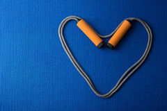 Heart from jumping rope on blue yoga mat background stock photo
