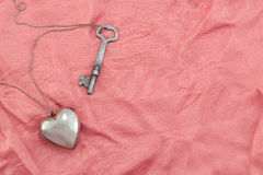 Heart and Key. A silver heart and key on a chain, laying on rumpled pink fabric Royalty Free Stock Image