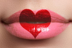 Heart kiss on the Lips. Beauty full lips with heart shape paint. Valentines Day. Beautiful make-up. Lipstick and lipgloss.  stock image
