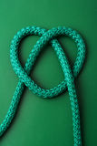 Heart from knot. Green heart from knot on dark green background Stock Photo