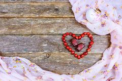 Heart laid out from buttons in the form of multi-colored paws. On a wooden laid out heart on an old wooden background Royalty Free Stock Image