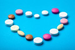 Heart laid out of pills. Heart laid out of pills on a blue background, drugs round and oval pills stock photo
