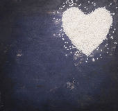 Heart, laid out rice on a blue rustic wooden background, top view, valentines day, place for text Stock Photography