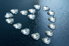 Heart laid out from a small crystal hearts on a blue background Stock Photo