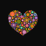 Heart laid out various flowers of different colors on black Royalty Free Stock Photography