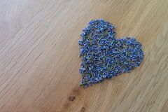 Heart of lavender on wooden table top. Heart formed out of dried lavender on a wooden table top with copy space royalty free stock photos