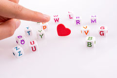 Heart between Letter cubes. Hand pointing at Heart between Letter cubes on a white background Royalty Free Stock Image