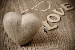 Heart and letters forming the word love, in sepia toning. A cardboard heart and wooden letters forming the word love on a rustic wooden surface, in sepia toning stock photo