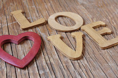 Heart and letters forming the word love on a wooden surface Royalty Free Stock Image
