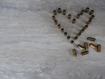 Heart lined with bullets on a light background, love theme of the holiday stock photo