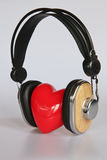 Heart listening to music. Abstract image of the love of music. Red heart listening to music with headphones Stock Photography