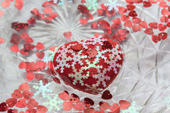Heart, little hearts and snowflakes floating in the water. A red heart. White snowflakes. A dish of water. Heart floats in water. Valentine`s day Stock Image
