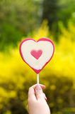 Heart lolipop. Heart shaped lolipop in hand on yellow natural background Royalty Free Stock Photo