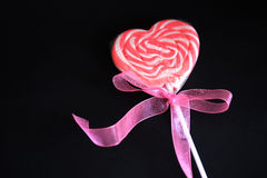Heart lollipop with pink ribbon on black. A pink heart lollipop with a cute ribbon on black stock photos
