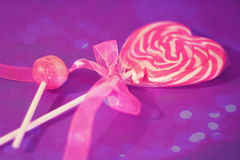 Heart lollipop with pink ribbon and bokeh overlay. A pink heart lollipop with cute ribbon with bokeh overlay stock images