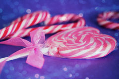 Heart lollipop with pink ribbon and bokeh overlay. A pink heart lollipop with cute ribbon with bokeh overlay royalty free stock photo