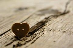 Heart love beauty sadness sorrow melancholy. Lonely heart sadness sorrow sad melancholy object grey wooden button sew background despair desperation hopelessness stock image
