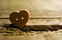 Heart love beauty sadness sorrow melancholy. Lonely heart sadness sorrow sad melancholy object grey wooden button sew background despair desperation hopelessness stock images