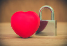 Heart of love and lock on wooden background Stock Images