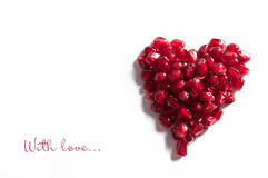 Heart with love. Heart from pomegranate seeds on the white background with the words with love Stock Images