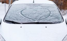 Heart love symbol on windscreen of car in snow. Front view of snowy car after winter blizzard royalty free stock photos
