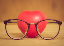 Heart of love wearing glasses on wooden Royalty Free Stock Photo