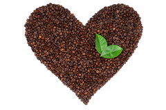 Heart made from coffee beans and green leaves. Heart made from coffee beans and green leaves isolated on white background stock photography