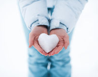 Heart made of snow. The heart of the snow in female hands royalty free stock photos