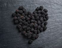 Heart made of blackberry on black slate. Top view. High resolution product royalty free stock photos