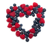 Heart made of blueberries and raspberries. On white Stock Images