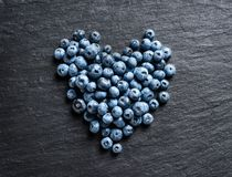 Heart made of blueberry on black slate. Stock Photos