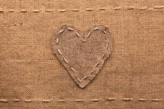 Heart made of burlap lies on a sacking background. Can be used as texture stock photography