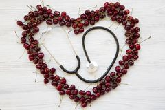 Heart made of cherries with stethoscope, top view. stock photos